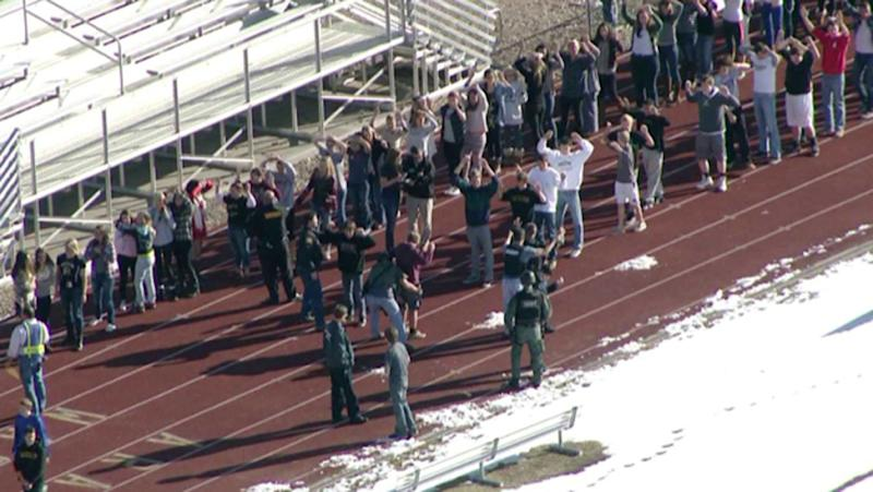 In this still image taken from video provided by Fox 31 Denver, students gather just outside of Arapahoe High School as police respond to reports of a shooting at Arapahoe High School in Centennial, Colo. Friday, Dec. 13, 2013. Colorado division of emergency management spokeswoman Micki Trost said her director went to the school and their weren't any more immediate details. (AP Photo/KDVR) MANDATORY CREDIT