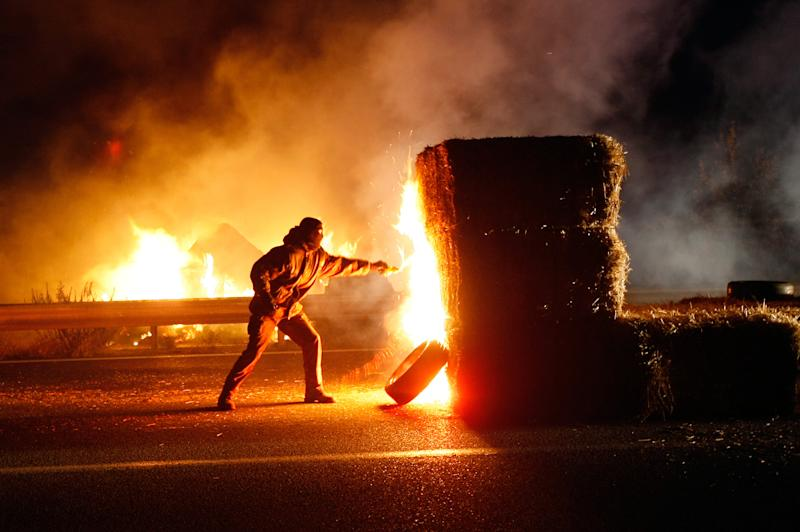 """A farmer burn straw bales as farmers block a main road, facing the police, in Arles, southern France, Friday, Nov. 15, 2013. Demonstrators are protesting against the controversial governmental environment """"eco-tax"""". (AP Photo/Claude Paris)"""