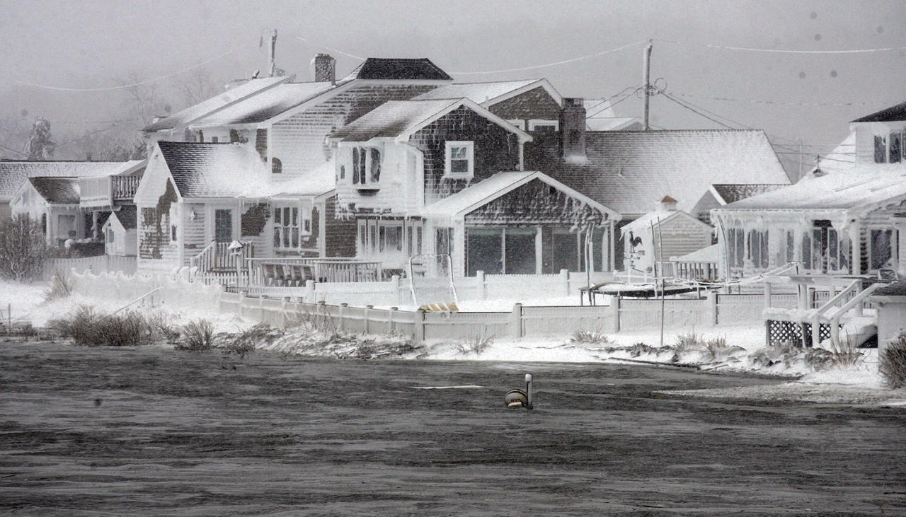 Wet snow coats houses along the South River at high tide in the Humarock coastal neighborhood of Scituate Mass. on Saturday, Feb. 9, 2013. A behemoth storm packing hurricane-force wind gusts and blizzard conditions swept through the Northeast overnight. (AP Photo/The Patriot Ledger, Greg Derr)