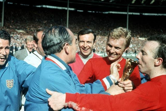 England captain Bobby Moore with manager Alf Ramsey as Nobby Stiles kisses the World Cup trophy