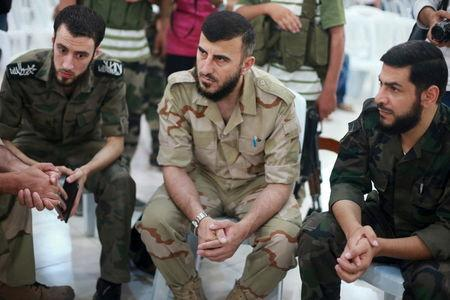 Zahran Alloush (C), commander of Jaysh al Islam, sits during a conference in the town of Douma, eastern Ghouta in Damascus, Syria August 27, 2014. REUTERS/Bassam Khabieh