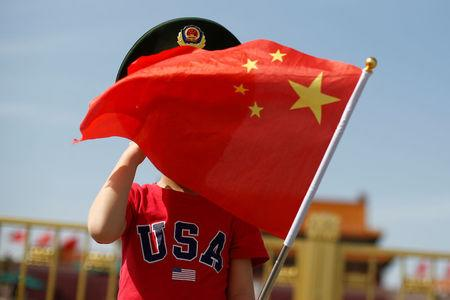 FILE PHOTO: A boy wearing an U.S. t-shirt waves a Chinese national flag in Tiananmen Square in Beijing