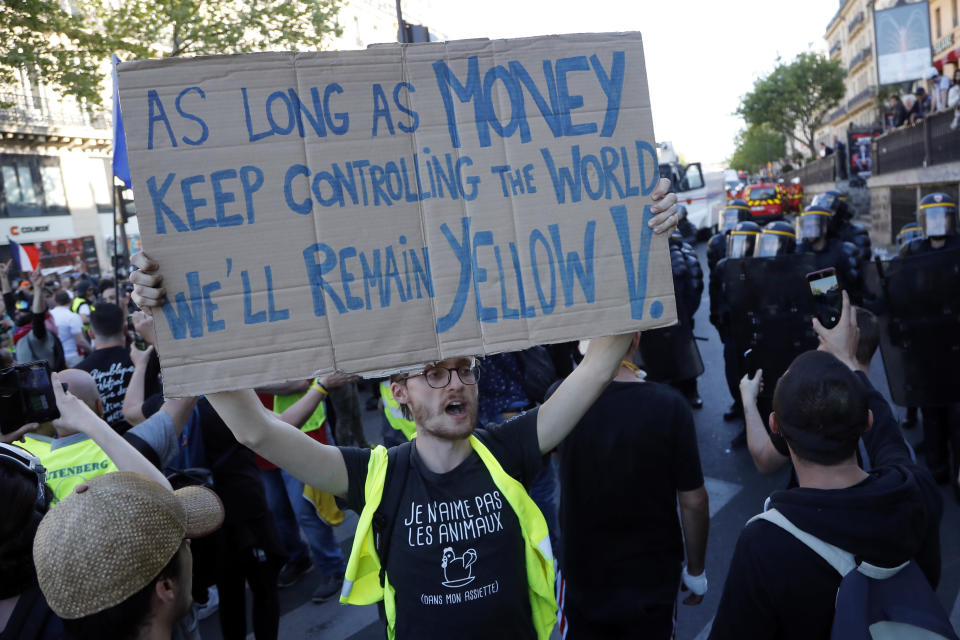 A man in a yellow vest holds up a sign at the Place de Republique during a yellow vest demonstration in Paris, Saturday, April 20, 2019. French yellow vest protesters are marching anew to remind the government that rebuilding the fire-ravaged Notre Dame Cathedral isn't the only problem the nation needs to solve. (AP Photo/Michel Euler)