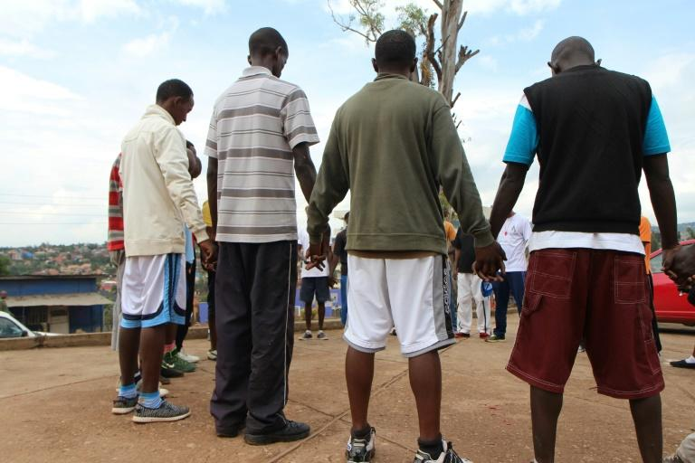 Burundi refugees living in Kigali pray after doing sports in the Rwandan capital on April 22, 2017
