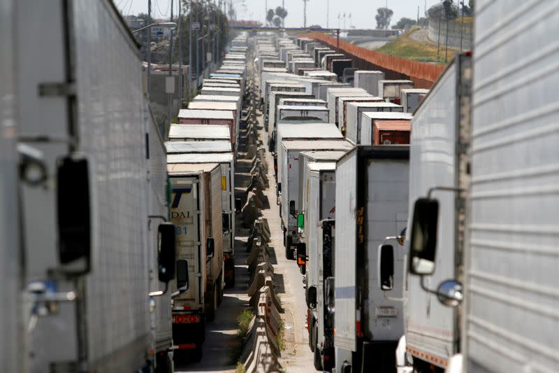 Trucks wait in a long queue for border customs control to cross into the U.S., caused by the redeployment of border officers to deal with a surge in migrants, at the Otay border crossing in Tijuana