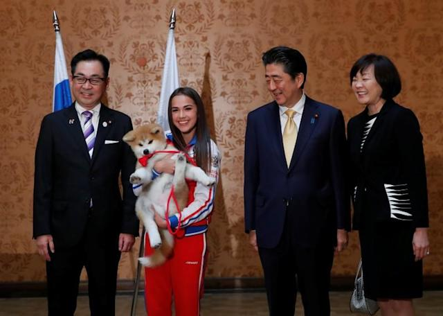Head of the Association for the preservation of the purity of the Akito breed Takashi, Russian figure skating gold medallist Zagitova, Japanese PM Abe and his wife Akie pose with an Akita Inu puppy presented to Zagitova, in Moscow