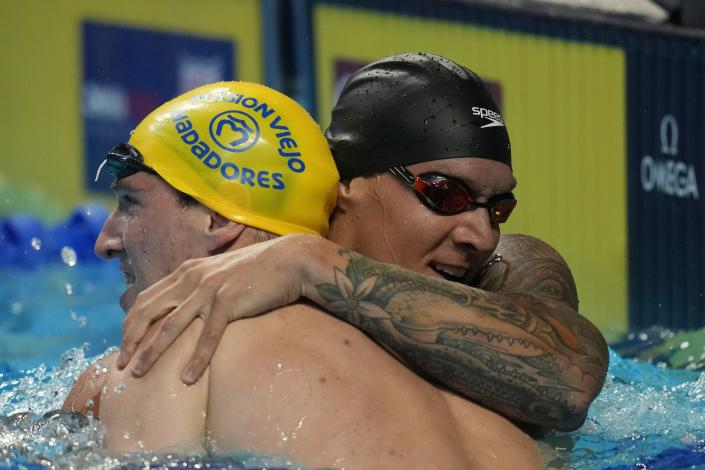 Caeleb Dressel hugs Zach Apple after winning the men's 100 freestyle during wave 2 of the U.S. Olympic Swim Trials on Thursday, June 17, 2021, in Omaha, Neb. (AP Photo/Charlie Neibergall)
