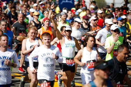 Apr 17, 2017; Hopkinton, MA, USA; Steve Cortes of Jensen Beach, FL puts up his hand as he crosses the start line at the 2017 Boston Marathon. Paul Rutherford-USA TODAY Sports
