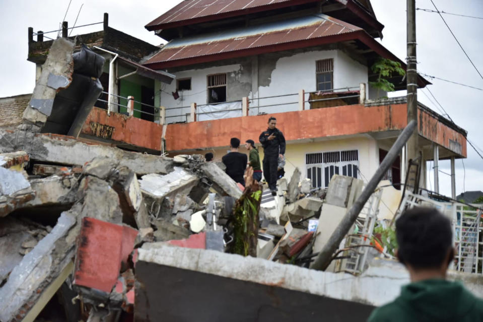 Rescuers search for survivors among the ruin of a building damaged by an earthquake in Mamuju, West Sulawesi, Indonesia, Friday, Jan. 15, 2021.A strong, shallow earthquake shook Indonesia's Sulawesi island just after midnight Friday, toppling homes and buildings, and triggering landslides. (AP Photo/Daus Thobelulu)