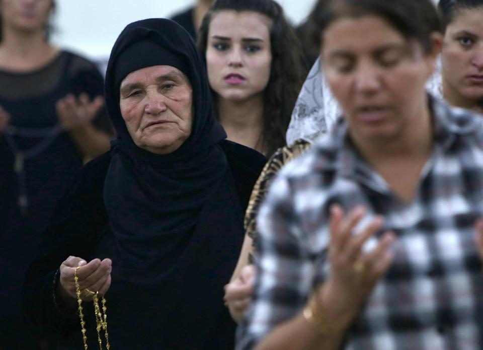 Iraqi Christians who fled the violence in Mosul pray at the MarAfram church in the village of Qaraqush, east of the city, on July 19, 2014 (AFP Photo/Safin Hamed)