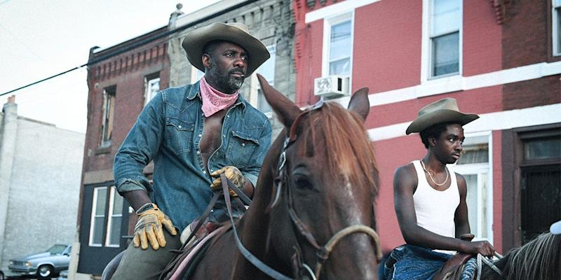 "Harp (Idris Elba, left) teaches his estranged son Cole (Caleb McLaughlin) how to ride a horse in ""Concrete Cowboy."""