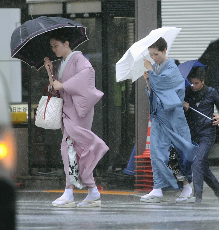 CORRECTS SPELLING OF KIMONOS - Two women in kimonos make their way through rains in Tokyo's Ginza shopping area on Wednesday Sept. 21, 2011 as powerful Typhoon Roke lashes central Japan with heavy rains and sustained winds of up to 100 mph (162 kph). The storm made landfall in the afternoon near the central Japanese city of Hamamatsu, about 125 miles (200 kilometers) west of Tokyo. (AP Photo/Kyodo News) JAPAN OUT, MANDATORY CREDIT, NO LICENSING IN CHINA, FRANCE, HONG KONG, JAPAN AND SOUTH KOREA