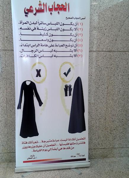 """This undated 2013 photo shows one of the signs that are posted throughout female university campuses, this one in Princess Nora University in Riyadh, Saudi Arabia, telling young women to dress in the conservative Islamic Wahabi tradition. Within their female-only campus grounds, women at Saudi Arabia's universities let loose, with trendy sneakers, colorful tops, a myriad of hairstyles. But in every student's bag is the black abaya robe they must cover themselves with when they step out of the university gates. The kingdom has spent billions to improve women's education, part of a broader drive to educate young Saudis for the workforce, but rights advocates say it will mean little as long as heavy restrictions on women remain. Arabic on the poster reads, """"Islamic veil, the right veil: 1-the garment should cover the woman's body. 2-the garment should not have too many embellishments. 3- it should be thick. 4- it should be loose. 5- the cloak should start from the crown of the head. 6-it should not look like men's clothing. 7- it should not look like the clothes of unbelievers."""" (AP Photo)"""