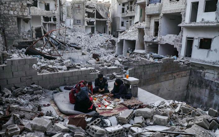 Syrian family eats a sunset 'iftar' meal after fasting during Ramadan, amid the ruins in Idlib province - AFP