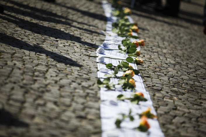 Roses are placed on sheets of paper with the names of those killed while trying to escape from East Berlin by crossing the Berlin Wall during a ceremony at the Brandenburg Gate in Berlin, August 13, 2011. The German capital marks the 50th anniversary of the building of the Berlin Wall, erected on August 13, 1961. (REUTERS/Pawel Kopczynski)