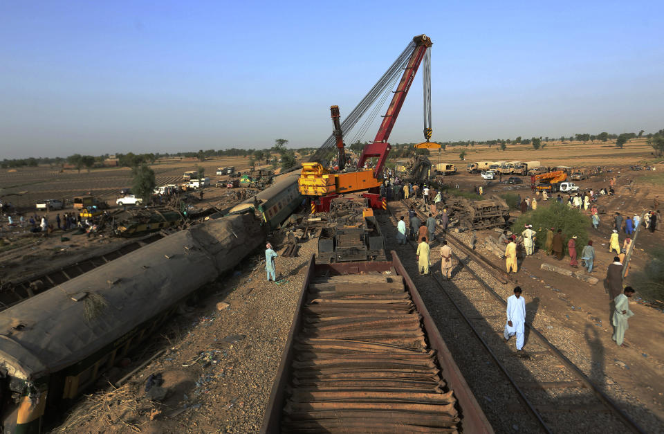 Railway workers remove wreckage to clear the track at the site of a train collision in the Ghotki district, southern Pakistan, Tuesday, June 8, 2021. The death toll from a deadly train accident in southern Pakistan jumped to dozens on Tuesday after rescuers pulled ea dozen more bodies from crumpled cars of two trains that collided on a dilapidated railway track a day ago, an official said, as rescue work continued even 24 hours after the incident to find any survivors. (AP Photo/Fareed Khan)