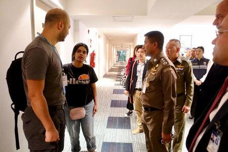 Saudi teen Rahaf Mohammed al-Qunun is greeted by Thai immigration authorities at a hotel inside Suvarnabhumi Airport in Bangkok