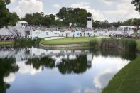 Jason Kokrak, right center, putts on the ninth green as Jordan Spieth, left, stands by a bunker and watches during the third round of the Charles Schwab Challenge golf tournament at Colonial Country Club in Fort Worth, Texas, Saturday May 29, 2021. (AP Photo/Ron Jenkins)