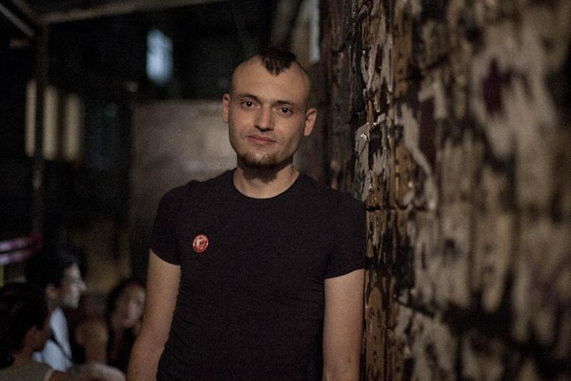 Israeli activist Sasha Boojor is seen during a gathering of activists for Animal rights in a club in Tel Aviv, Wednesday, June 26, 2013. Boojor squirmed and struggled as black-clad masked men yanked him out of a cage and branded him with a hot iron. While the smell of seared flesh was disturbing, he said, this shocking and painful act was worth it: He was showing solidarity with animals that suffer branding on farms around the world. (AP Photo/Dan Balilty)