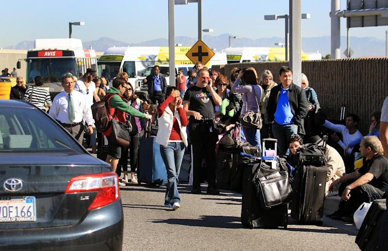 Passengers evacuate the Los Angeles International Airport on Friday Nov. 1, 2013, in Los Angeles. Shots were fired at Los Angeles International Airport, prompting authorities to evacuate a terminal and stop flights headed for the city from taking off from other airports. (AP Photo/Ringo H.W. Chiu)