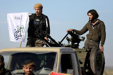 FILE PHOTO: Turkish-backed Syrian rebels stand on the back of a truck at Manbij countryside, Syria December 29, 2018. REUTERS/Khalil Ashawi/File Photo