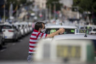 A taxi driver wearing a face mask to prevent the spread of coronavirus stands during a taxi drivers protest in downtown Madrid, Spain, Tuesday, June 30, 2020. Taxi drivers are demanding assistance due to lack of clients and private hire. (AP Photo/Manu Fernandez)