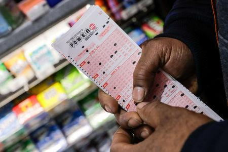 A customer buys tickets for the Powerball lottery in New York City, U.S., March 17, 2017. REUTERS/Jeenah Moon