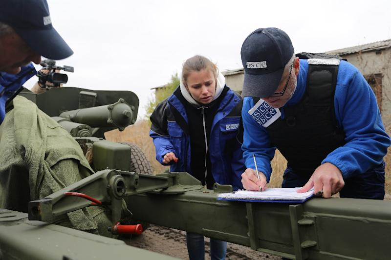 OSCE (Organization for Security and Co-operation in Europe) observers check a column of fifteen MT-12 Rapira 100-mm anti-tank guns being withdrawn by pro-Russian separatists from Donetsk to the village of Zelene, Donetsk region, on October 28, 2015