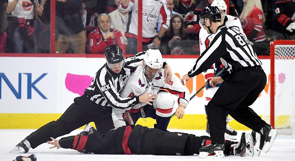 """Washington's <a class=""""link rapid-noclick-resp"""" href=""""/nhl/players/3637/"""" data-ylk=""""slk:Alex Ovechkin"""">Alex Ovechkin</a> is pulled off a motionless Andrei Svechnikov of the <a class=""""link rapid-noclick-resp"""" href=""""/nhl/teams/carolina/"""" data-ylk=""""slk:Carolina Hurricanes"""">Carolina Hurricanes</a> during the first period of Game 3 of their first round series on Monday. (Photo by Grant Halverson/Getty Images)"""