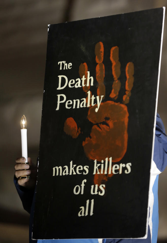 A death penalty opponent holds a sign during a vigil outside St. Francis Xavier Church, Tuesday, Nov. 19, 2013, in St. Louis. A federal judge on Tuesday granted a stay of execution to Missouri death row inmate Joseph Paul Franklin just hours before his scheduled death, citing concerns over a new execution method. (AP Photo/Jeff Roberson)