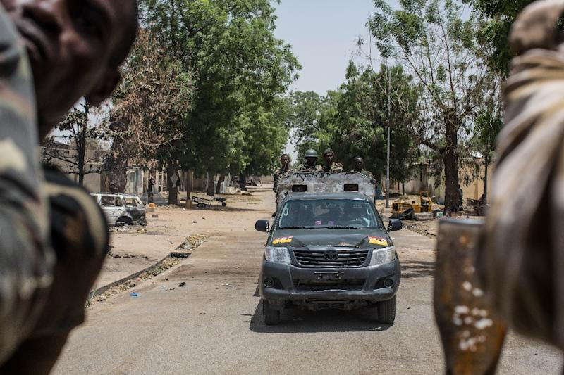 Nigerian troops patrol in Baga, Nigeria, on March 25, 2015, as the military has retaken the city from Boko Haram, but signs of mass killings carried out by Boko Haram earlier this year remain (AFP Photo/Nichole Sobecki)