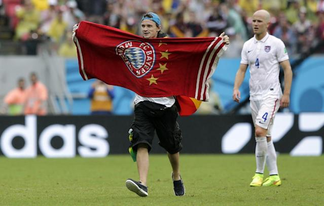 A Bayern Munich supporter runs onto the pitch during the group G World Cup soccer match between the USA and Germany at the Arena Pernambuco in Recife, Brazil, Thursday, June 26, 2014. (AP Photo/Matthias Schrader)