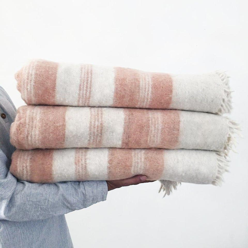 """<p>hecho-shop.com</p><p><strong>$145.00</strong></p><p><a href=""""https://www.hecho-shop.com/product/blush-handmade-striped-momos-wool-blanket"""" rel=""""nofollow noopener"""" target=""""_blank"""" data-ylk=""""slk:Shop Now"""" class=""""link rapid-noclick-resp"""">Shop Now</a></p><p><a href=""""https://www.hecho-shop.com/"""" rel=""""nofollow noopener"""" target=""""_blank"""" data-ylk=""""slk:Hecho Shop"""" class=""""link rapid-noclick-resp"""">Hecho Shop</a>, started by Ehren Seeland, works with artisans in Mexico and Guatemala to create unique homewares and accessories that cater to a modern market and help sustain the community of makers. One of our favorites? The brushed wool blanket handwoven in the highlands of Guatemala using techniques dating back centuries.</p>"""