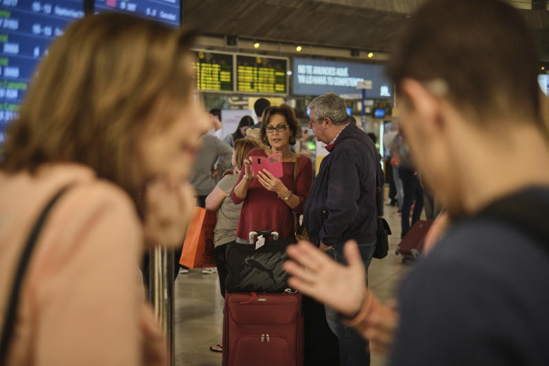 Passengers wait in the airport in Santa Cruz de Tenerife, Spain, Sunday, Feb. 23, 2020. Flights leaving Tenerife have been affected after storms of red sand from Africa's Saharan desert hit the Canary Islands. (AP Photo/Andres Gutierrez)