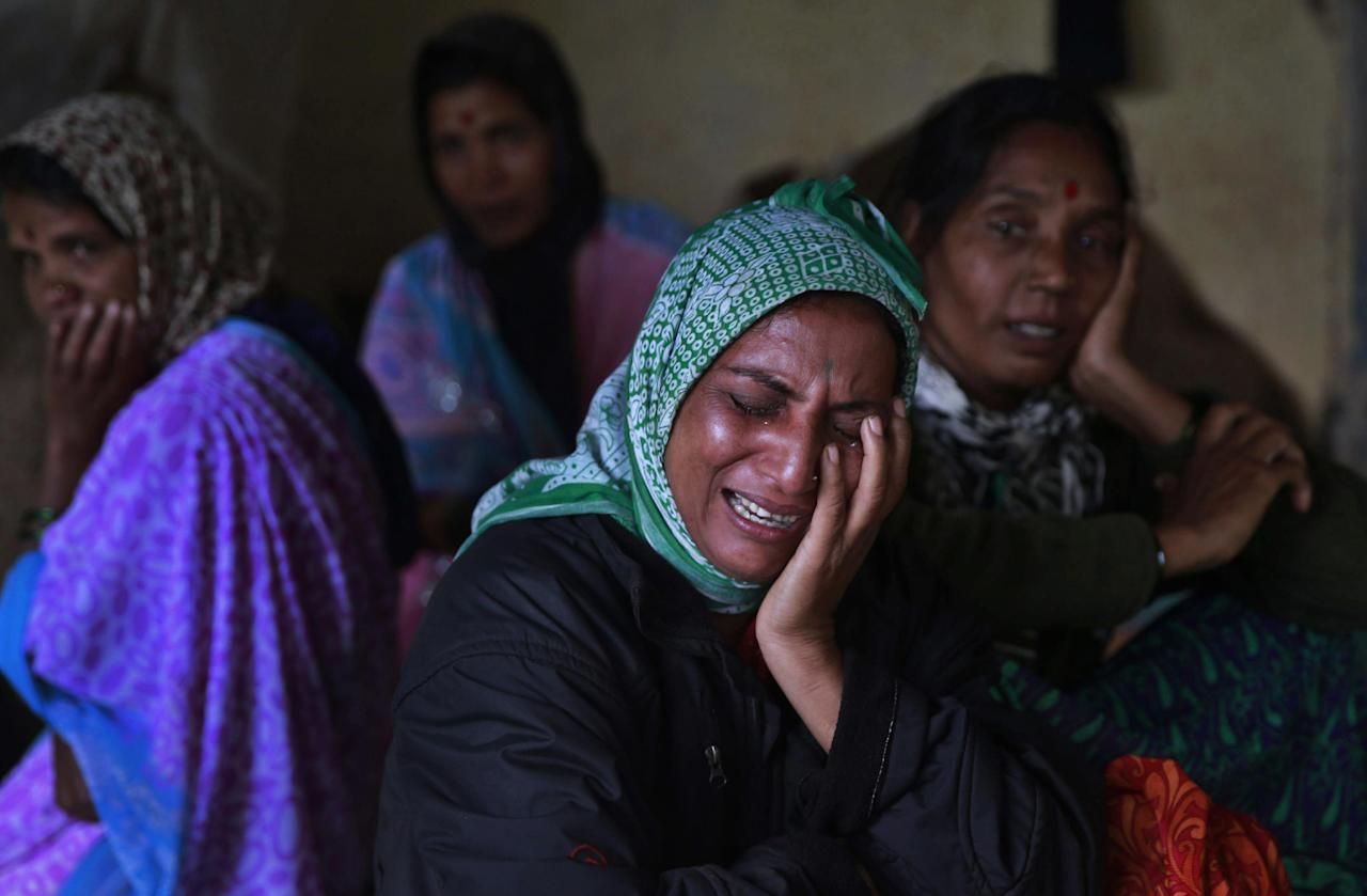 Relatives wail after seeing the body of a victim after a massive landslide in Malin village in Pune district of western Maharashtra state, India, Thursday, July 31, 2014. Two days of torrential rains triggered the landslide early Wednesday, killing more than two dozen people and trapping more than 150, authorities said. (AP Photo/Rafiq Maqbool)