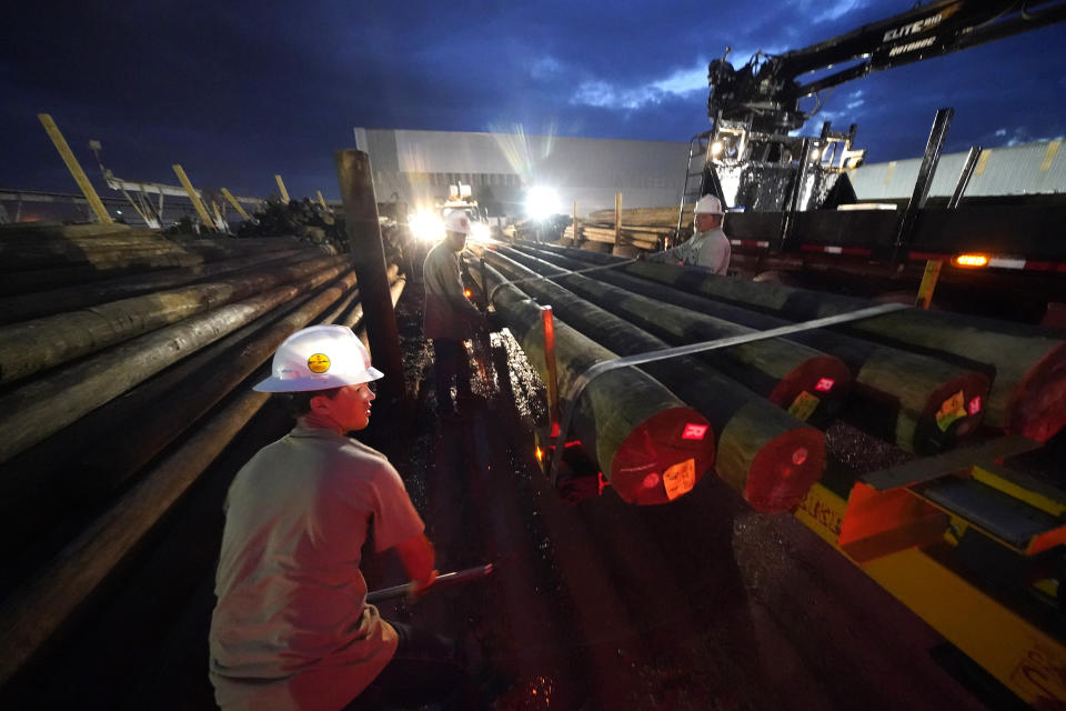 A worker straps down utility poles that were just loaded on their truck before they head out to restore power at dawn, at a tent city for electrical workers in Amelia, La., Friday, Sept. 17, 2021. In the wake of hurricanes, one of the most common and comforting sites is the thousands of electric workers who flow into a battered region when the winds die down to restore power and a sense of normalcy. (AP Photo/Gerald Herbert)