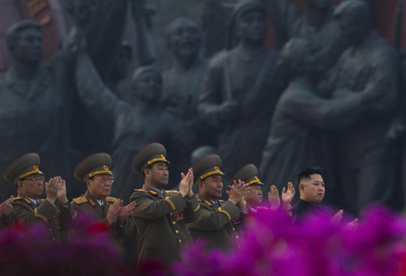 North Korean leader Kim Jong Un, far right, applauds with senior military officials as citizens wave flowers at an unveiling ceremony for statues of the late leaders Kim Il Sung and Kim Jong Il in Pyongyang, North Korea, Friday, April 13, 2012. (AP Photo/David Guttenfelder)
