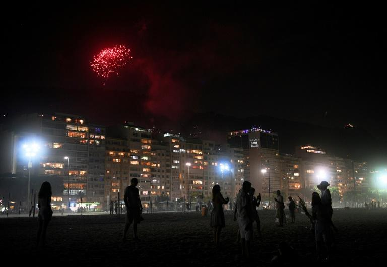 Revellers watch New Year's fireworks launched from a nearby favela on an almost empty Copacabana beach in Rio de Janeiro, Brazil