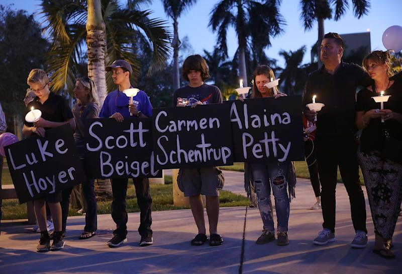 Mournershold signs with the names of some of the 17 people killed during a shooting at Marjory Stoneman Douglas High School at a candlelight vigil on Friday in Boca Raton, Florida. (Joe Raedle via Getty Images)
