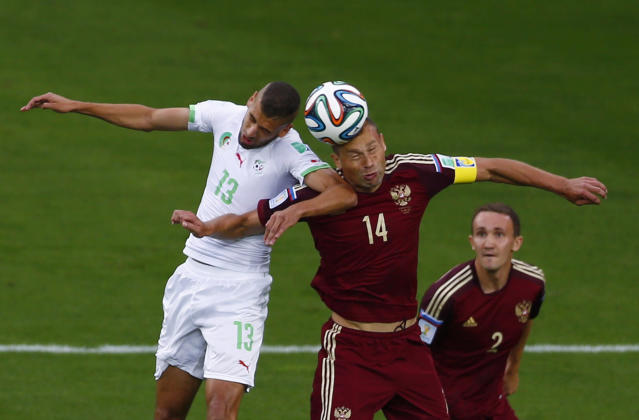 (L-R) Algeria's Islam Slimani and Russia's Vasili Berezutskiy jump for the ball as Russia's Alexey Kozlov watches during their 2014 World Cup Group H soccer match at the Baixada arena in Curitiba June 26, 2014. REUTERS/Amr Abdallah Dalsh (BRAZIL - Tags: SOCCER SPORT WORLD CUP)
