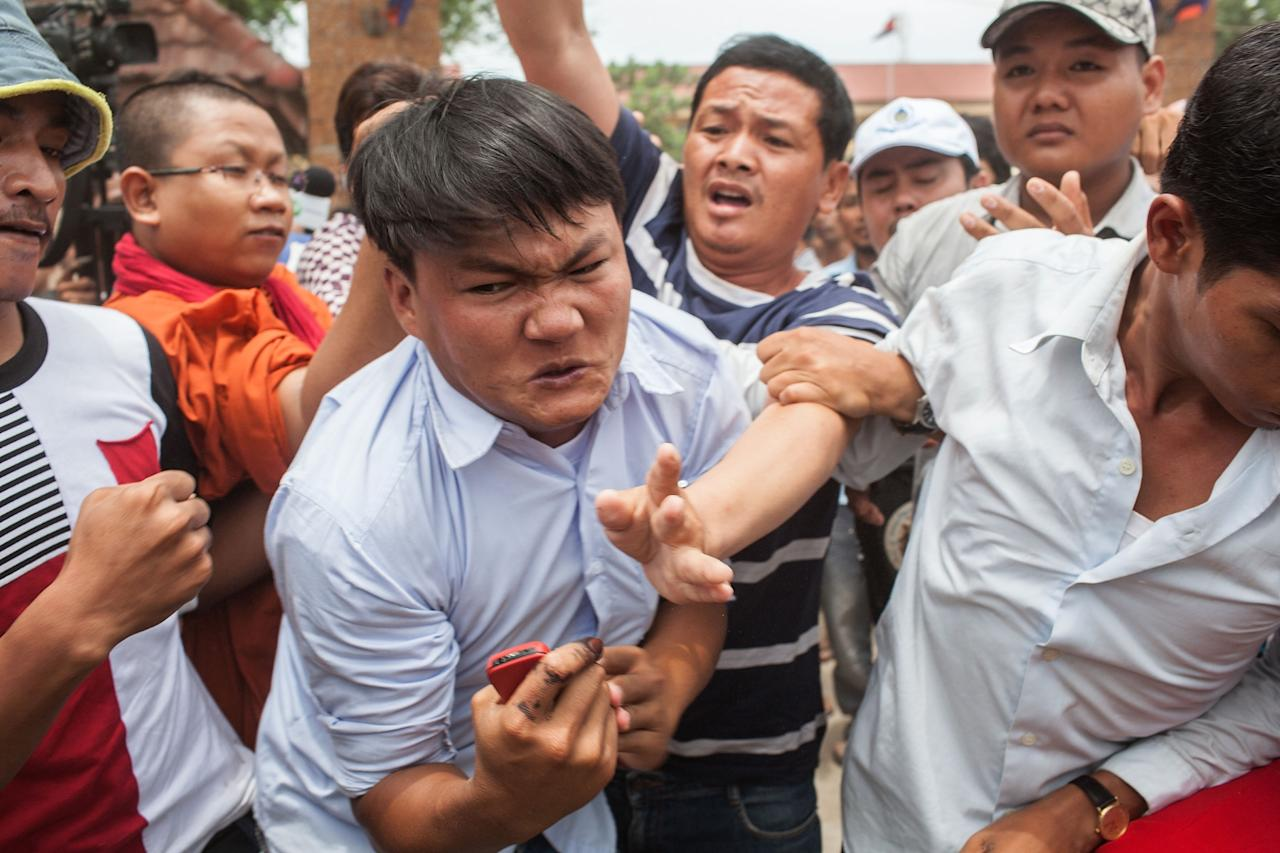 PHNOM PENH, CAMBODIA - JULY 28: A man is attacked by a mob in front of a polling station after being accused of striking a monk during an altercation between voters and the National Election Committee employee in charge of the polling station (the National Election Committee staff member was accused of denying people the right to vote) during the Cambodian general elections on July 28, 2013 in Phnom Penh, Cambodia. Cambodians go to the polls today in the fifth parliamentary election since 1993. 123 seats in the National Assembly are up for grabs to eight listed parties, with the main contenders being the ruling Cambodian Peoples Party (CPP) and the leading opposition Cambodia National Rescue Party (CNRP) led by Sam Rainsy. (Photo by Nicolas Axelrod/Getty Images)