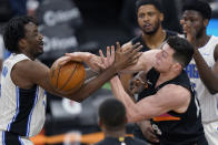 Orlando Magic forward Al-Farouq Aminu, left, and San Antonio Spurs forward Drew Eubanks, right, battle for control of a rebound during the second half of an NBA basketball game in San Antonio, Friday, March 12, 2021. (AP Photo/Eric Gay)
