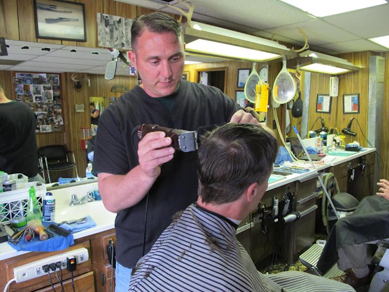 In this May 23, 2013, photo, barber BJ McClead, whose daughter Hayden was a friend of slain 16-year-old Skylar Neese, cuts a customer's hair at John's Barber Shop in Star City, W.Va. People in the small West Virginia town wondered for months about Neese. She vanished after slipping out the bedroom of her Star City home last summer, but few believed she'd run away. The truth emerged when one of Neese's friends admitted plotting with another teenage girl to kill her, a revelation that shocked even police. (AP Photo/Vicki Smith)