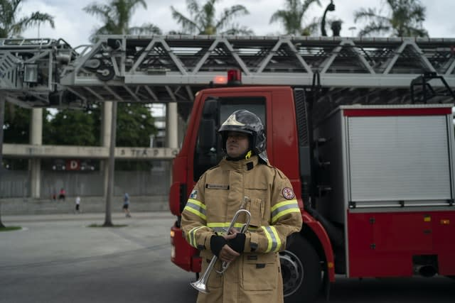 Firefighter Elielson Silva arrives to play his trumpet from the top of a ladder for residents cooped up at home during lockdown in Rio de Janeiro, Brazil