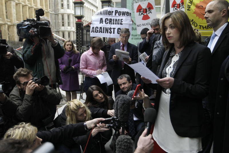 Singer Charlotte Church, right, speaks to the media outside the High Court in London after hearing the reading of a statement setting out the terms of the settlement for phone hacking damages claim against News International, Monday, Feb. 27, 2012. Church, who testified before a media inquiry of being hounded by Rupert Murdoch's journalists when she was a teen singing sensation, received 600,000 pounds ($951,000) Monday in a phone hacking settlement from News International and said she had been sickened by what she had learnt about intrusion into her private life. (AP Photo/Sang Tan)
