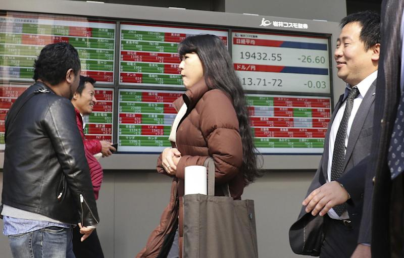 People walk past an electronic stock indicator of a securities firm in Tokyo, Tuesday, Feb. 14, 2017. Shares in Asia fell back after an early rally on Tuesday, as investors awaited comments to Congress by Federal Reserve chair Janet Yellen. (AP Photo/Shizuo Kambayashi)