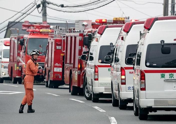 A rescue worker stands by beside ambulances near the Tsukui Yamayuri En care centre (AFP Photo/Jiji Press )