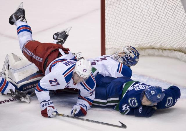 New York Rangers defenseman Ryan McDonagh (27) and Vancouver Canucks center Jordan Schroeder (45) fall over Rangers goalie Henrik Lundqvist during the second period of an NHL hockey game Tuesday, April 1, 2014, in Vancouver, British Columbia. (AP Photo/The Canadian Press, Jonathan Hayward)