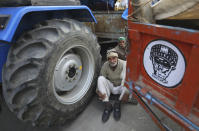 Indian farmers sit near their tractor after arriving at the Delhi-Uttar Pradesh border for Tuesday's tractor rally in New Delhi, India, Monday, Jan. 25, 2021. Thousands of farmers gathered on the borders of Delhi for a massive tractor rally on Tuesday against the three contentious farm laws when India will celebrate its Republic day with a military and cultural parade. The two-month-old old blockade of highways connecting the capital with the country's north continues as the talks have remained deadlocked with the government refusing to scrap the new agricultural reform laws which the farmers say will benefit large corporations. (AP Photo/Manish Swarup)