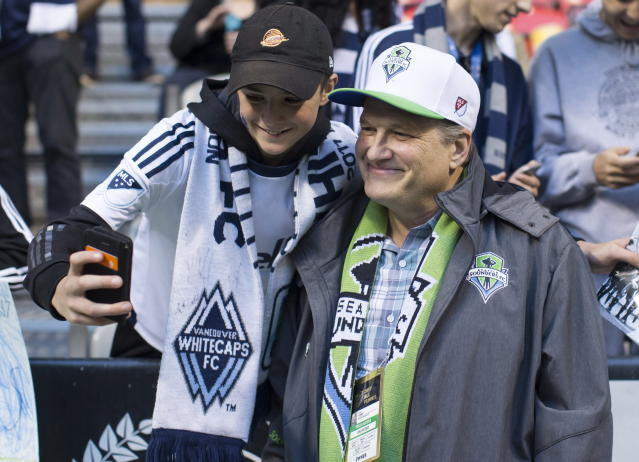Seattle Sounders co-owner Drew Carey (R) poses for a photo with a Vancouver Whitecaps fan before an MLS playoff game on Oct. 29, 2017. (AP)